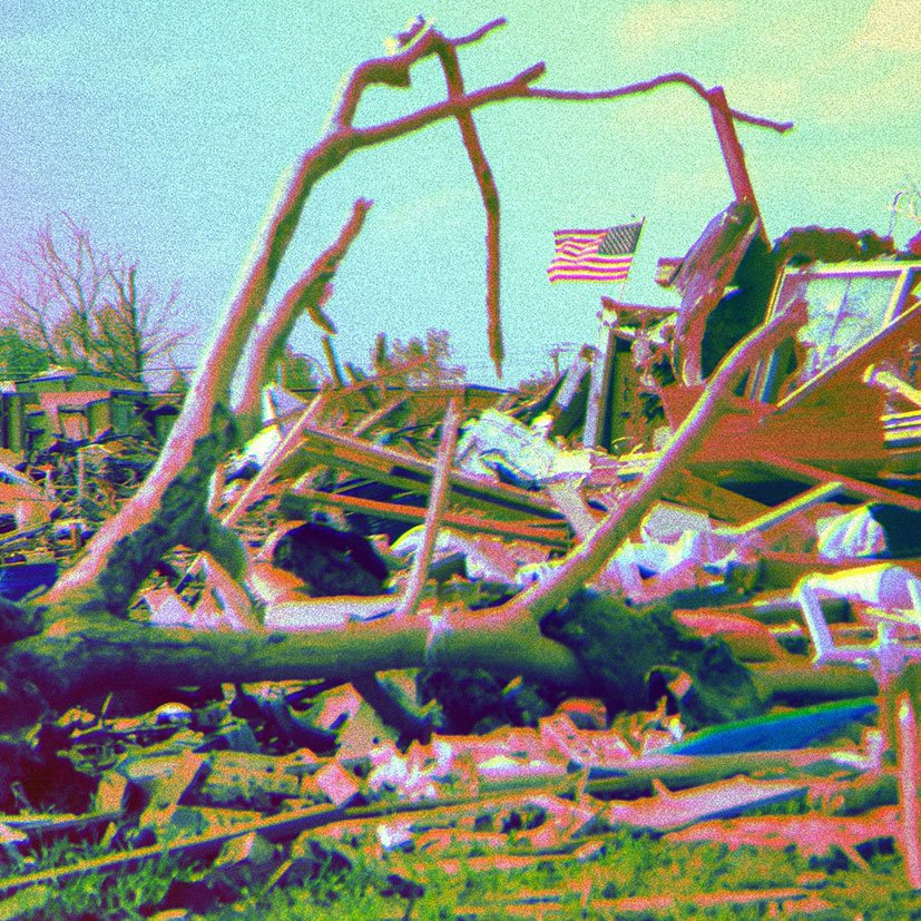 A destroyed home with an American flag still standing.
