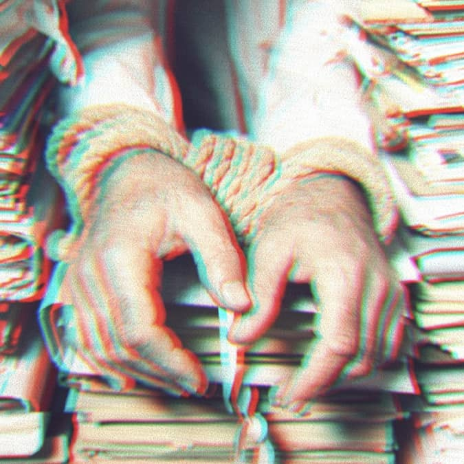 Glitchy photo of 3 stacks of paperwork. A man's wrists are bound by rope handcuffs and rest on the middle stack of papers.
