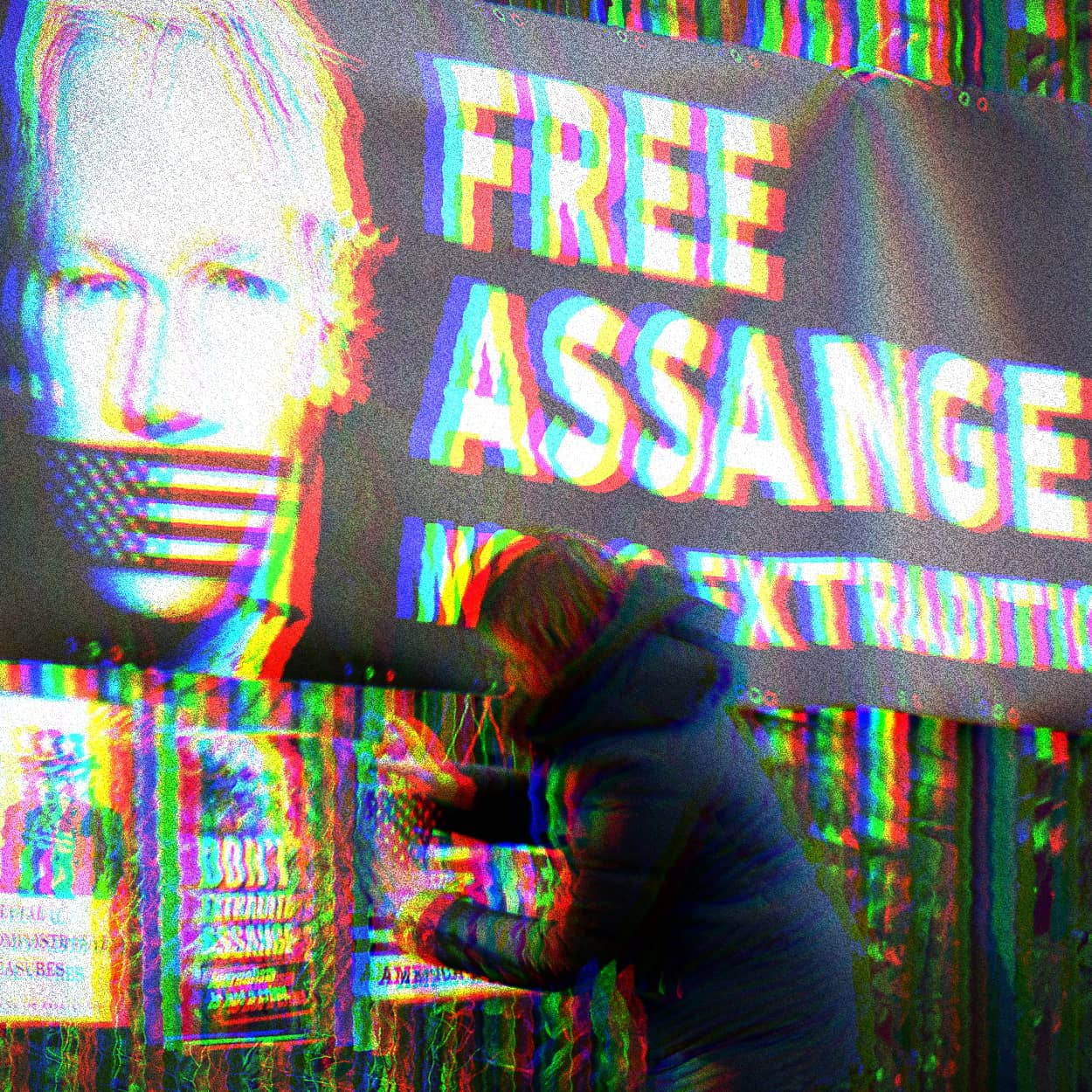 Glitchy photo of a banner with a photo of Julian Assange with American Flag tape over his mouth. Banner text says, 'Free Assange. No U.S. Extradition.' Below the banner a woman is adding another pro-Assange poster.