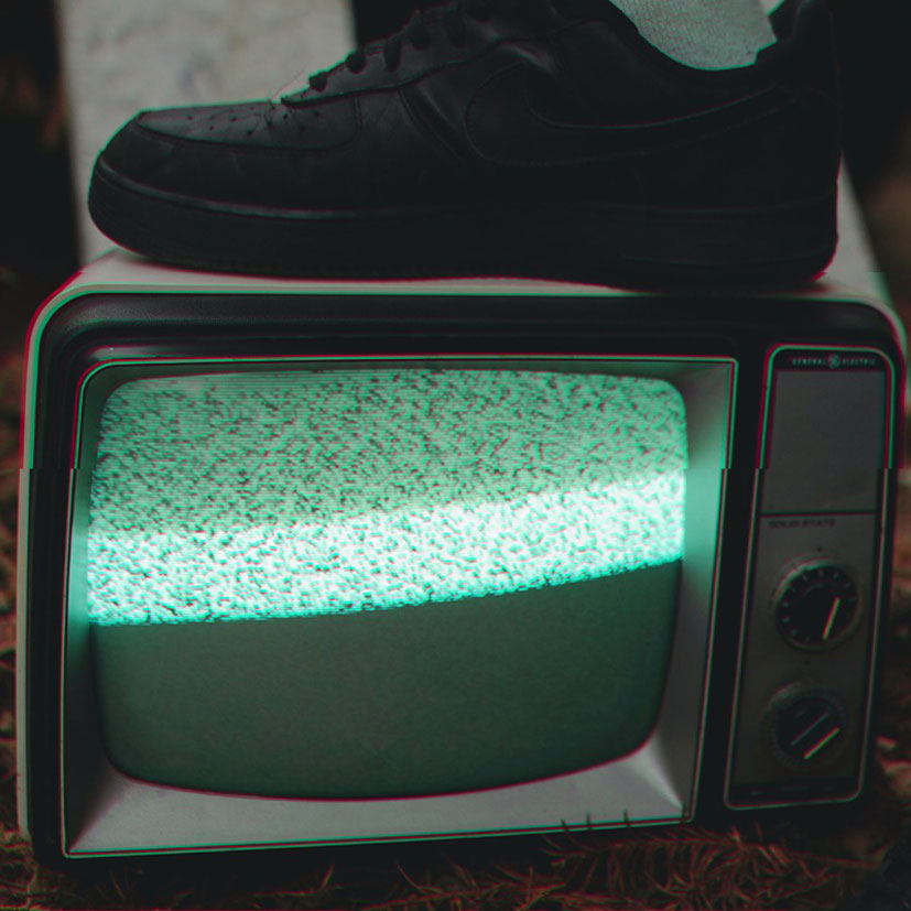 Person with their foot on a tv.