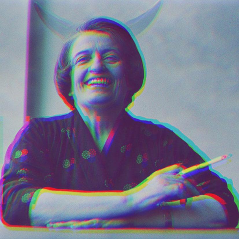 Ayn Rand smoking and laughing.