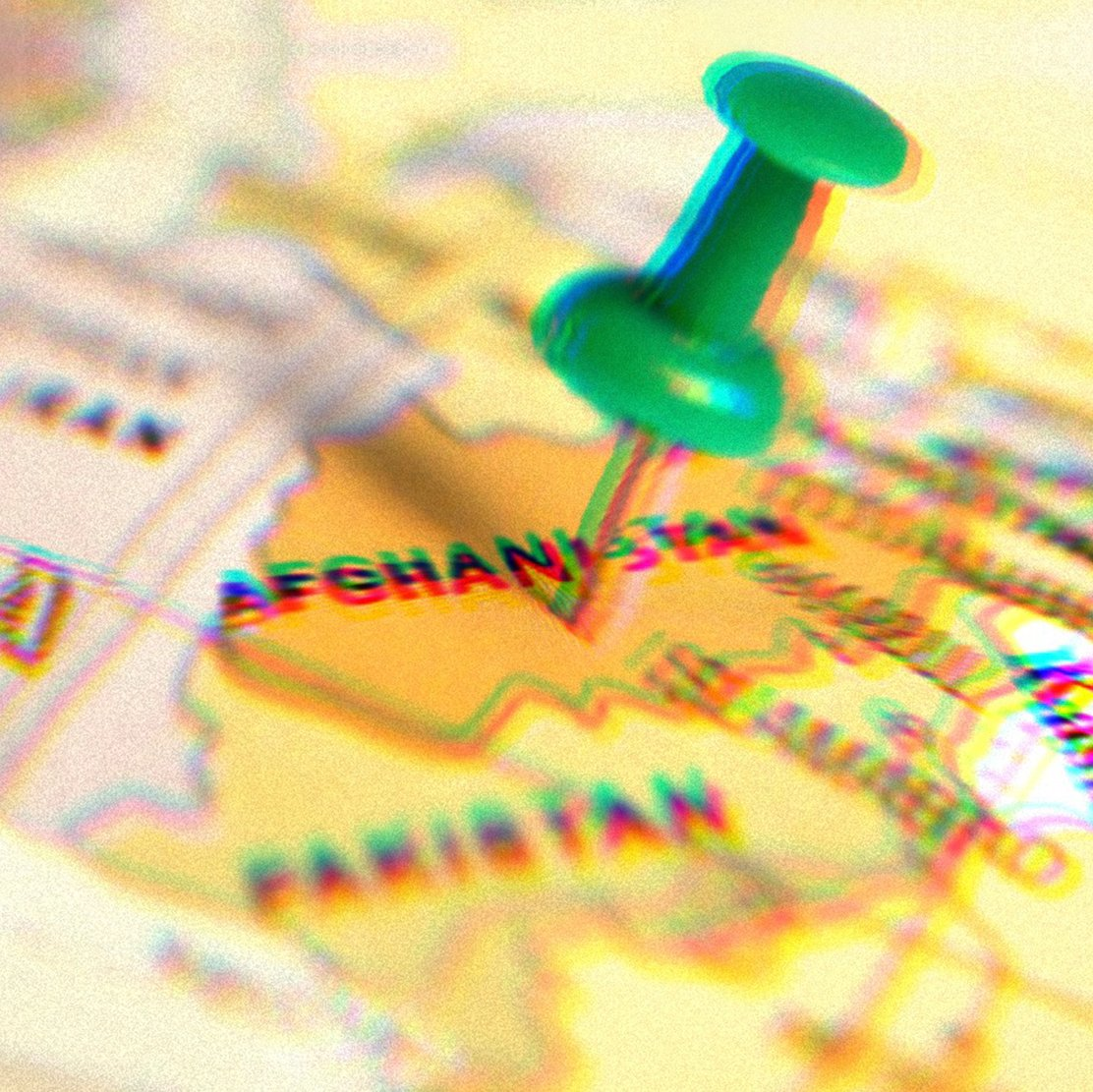 Green pushpin pressed into a map, the pin is sticking into Afghanistan.